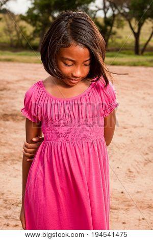 Happy Hispanic little girl playing outside on a farm.