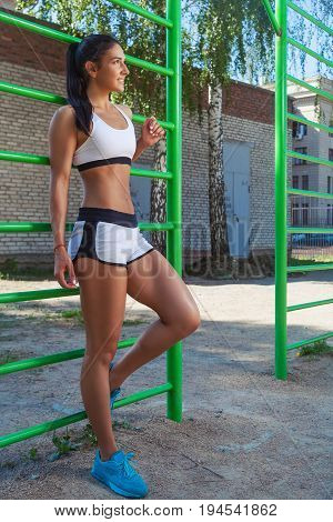 Young sporty brunette woman in short shorts and sports posing next to sports horizontal bars on a summer day