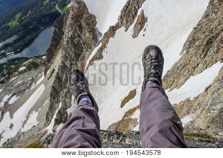A hiker dangles his legs precariously over the edge of a cliff in the Rocky Mountains.
