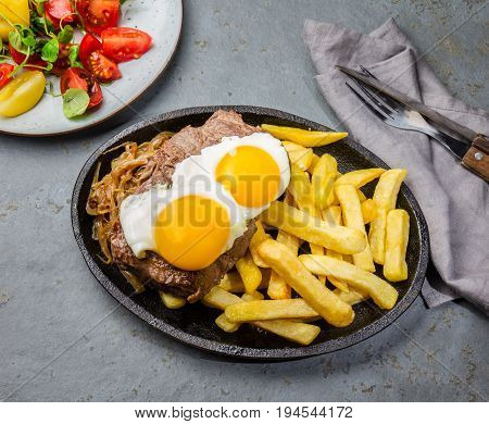Peruvian Latin American food. Lomo a lo pobre. Beef whit fried potatoes french fry and eggs