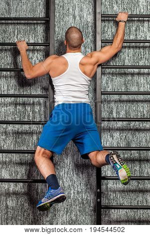 a man climbs up the stairs. Vertical ladder against the wall. Background - gray texture