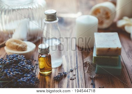 Natural spa products and decor for bath. Handmade herbal soap, organic oil, lavender, loofah and beauty products on wooden desk, closeup photo.