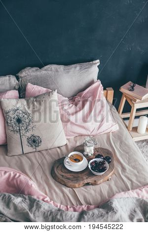 Black loft bedroom and pastel bedding set. Unmade bed with breakfast and reading on tray. Interior decor over blank blackboard wall with copyspace. Cozy modern living space.