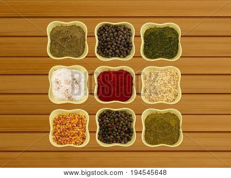 Collection of spices in ceramic bowls on a wooden background fragrant paprika paprika fennel and coriander