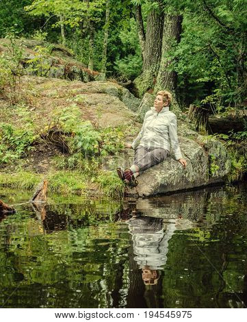 Woman is sitting on a rock by a small stream on Upper Peninsula, Michigan