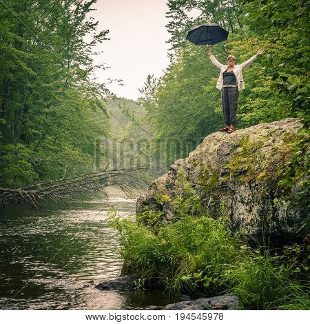 Happy woman with umbrella standing on a rock by the river in the rain