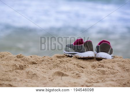 Women sandals on sand beach on day time.