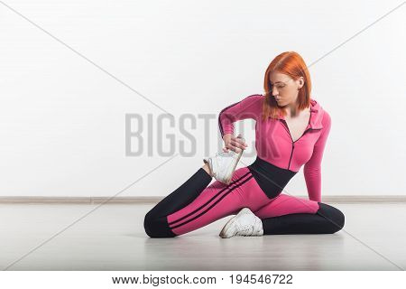 Sporty flexible woman doing exercises in the gym