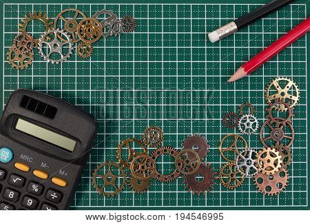 Business success concept. Metal gears on cutting board mat background with calculator and pencil for business planning create group work connection innovation and team work concept.