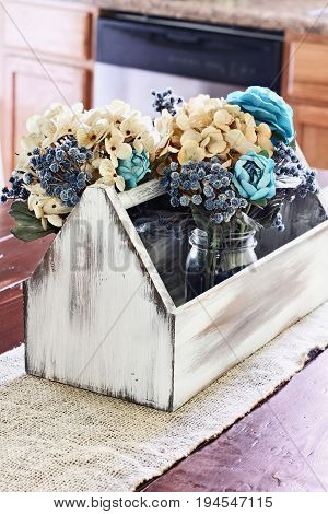 Interior rustic kitchen farmhouse table with old vintage wooden toolbox with faux flowers in a mason jar. Extreme shallow depth of field.
