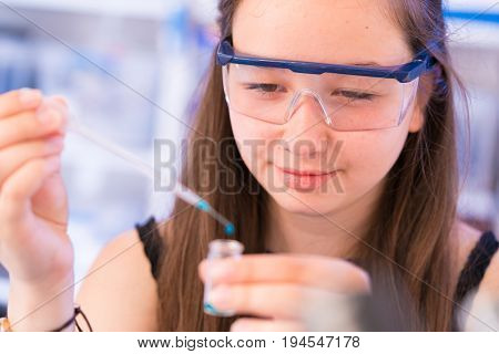 A teenage girl in a school laboratory in chemistry and biology classes