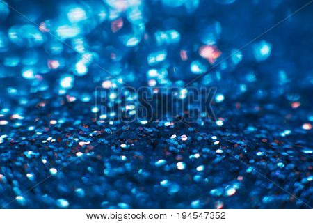 Abstract shining glitters blue makeup background. Blurred multicolored tinsel, selective focus with shallow depth of field. Glisten foil backdrop, christmas magic , eyeshadow closeup concept