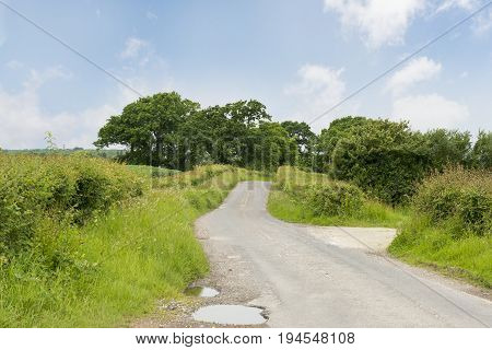 Narrow Country Road With A Pothole