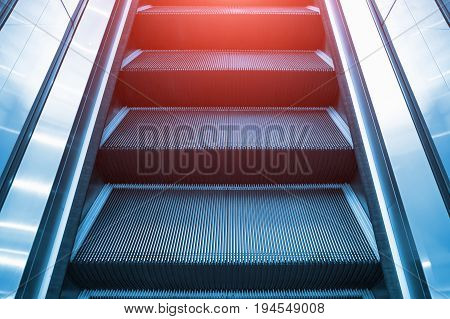 Escalator and step inside shopping mall or building.