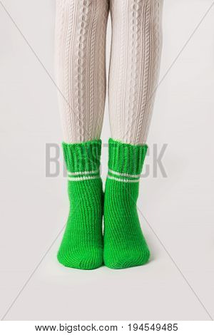 Female legs in white stockings and green knitted socks.