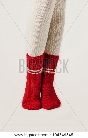 Female legs in white stockings and red knit socks.