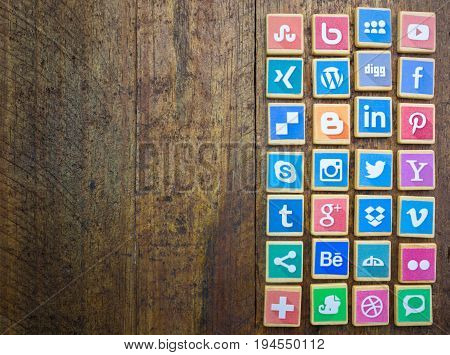 QUEENSTOWN SOUTH AFRICA - 09 APRIL 2017: Social Media logotype popular collection printed and place on wood scrabble game pieces isolated on rustic brown wooden floor planks