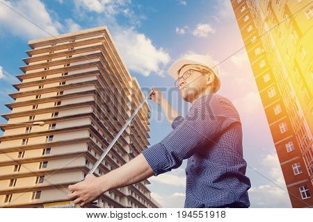 Male construction builder worker - foreman is an engineer in a protective helmet, glasses on the background of building a house with a crane Ruler measures. Concept calculation of construction time and cost.