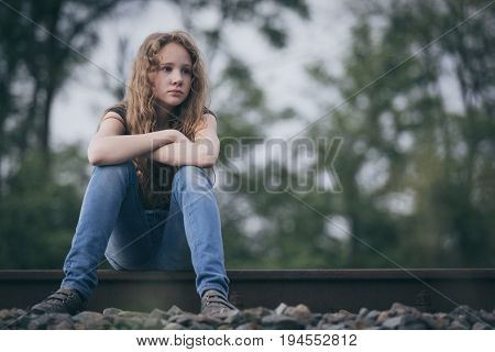 Portrait Of Young Sad Ten Girl Sitting Outdoors At The Day Time.
