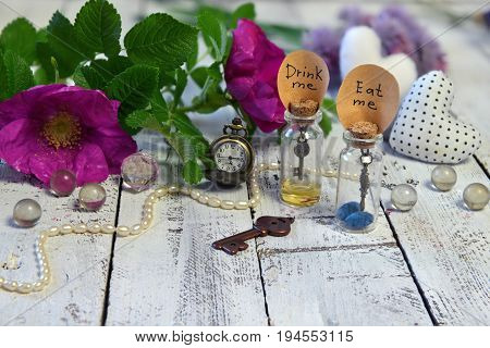 Tiny bottles with tags eat me and drink me, clocks, key and wild roses on planks. Alice in Wonderland background, fairy tale abstract concept with summer flowers
