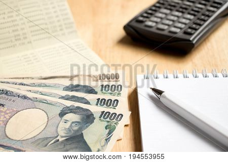 Bank passbook with japanese yen and book with pen calculator on wood table background