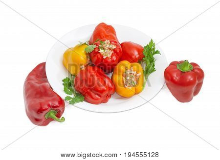 Cooked stuffed red and yellow bell peppers and twigs of parsley and cilantro on a white dish and two uncooked red bell peppers separately beside on a light background