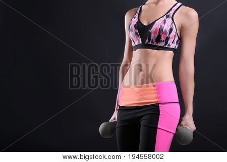 Woman in sport suit holding dumbbells on dark background