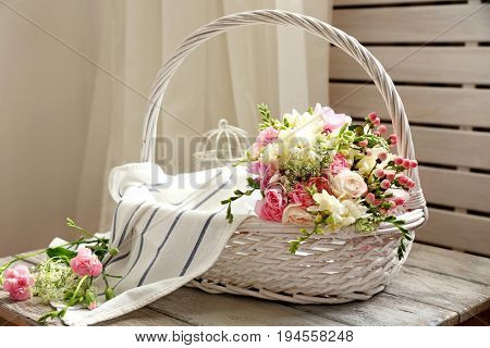 Beautiful bouquet with freesia flowers in basket on table