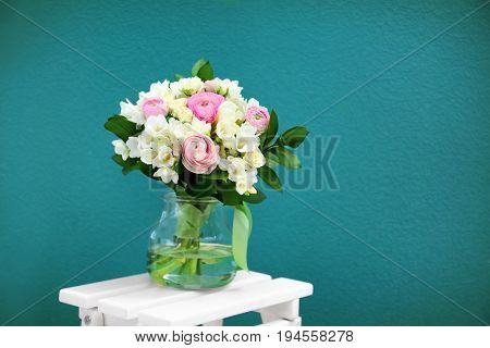 Beautiful bouquet with white freesia on color background