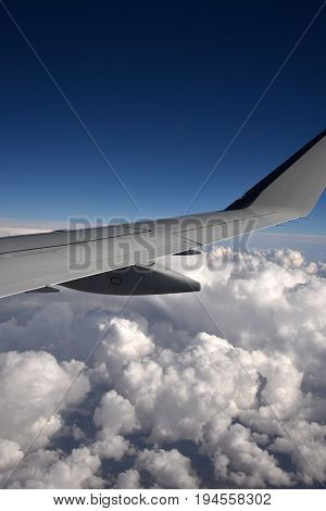 An airplane skimming above the cloud layer taken from the cabin of the aircraft