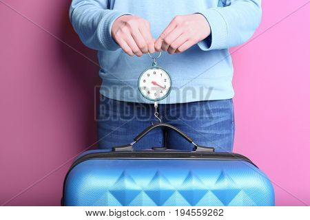 Woman weighting heavy luggage on color background