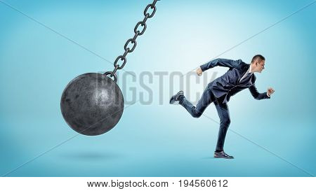A small businessman running away from a giant black wrecking ball on a chain. Business trouble. Leaving problems behind. Run away from crisis.