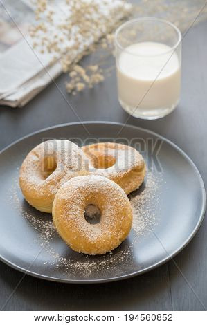 Sugary Donut On A Black Plate And Glass Of Milk On A Dark Table Background. In A Windows Light. Brea