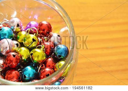 colorful bells in glass bottle on wooden table