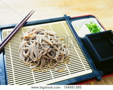 Cold soba [buckwheat noodles] served on a wickerwork platter and eaten after being dipped in a cold sauce/Eating Chilled Buckwheat Noodles Soba with chopsticks Japanese food