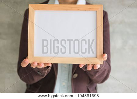 Blank wooden photo Frame in the woman's hand .