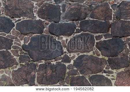 Background of dark stones of red terracotta color fastened by cement wall