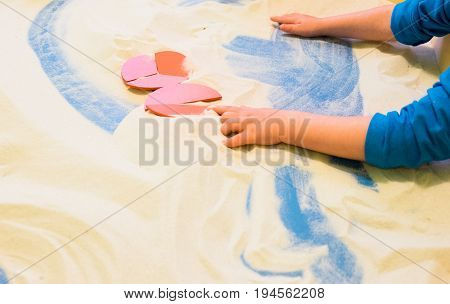 a boy plays with sand in the children's sandbox to develop lessons for toddlers connects fractional parts in a single round