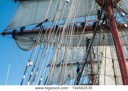 Sail, mast a and rigging. Some sailors on it