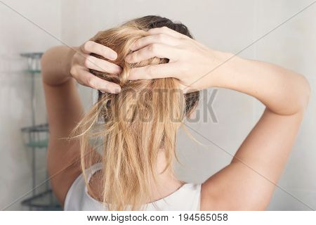 Beautiful young woman is styling hair in bathroom at home