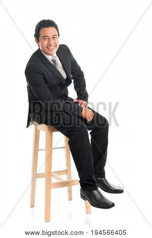 Full body portrait of good looking young Southeast Asian businessman sitting on high chair, isolated on white background.