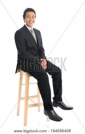 Full body portrait of handsome young Southeast Asian businessman sitting on high chair, isolated on white background.