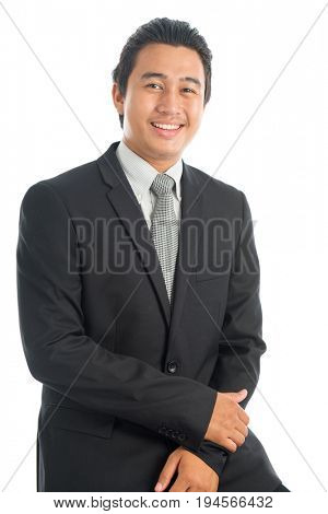 Portrait of happy young Southeast Asian businessman sitting on chair, isolated on white background.