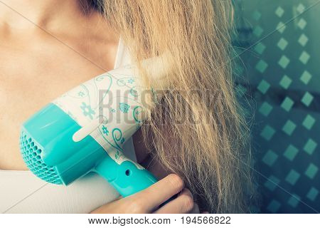 Beautiful sensual young woman is drying her hair with dryer