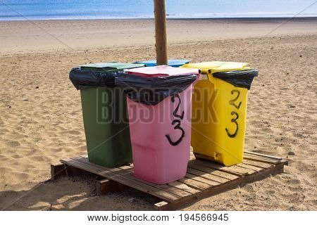 Four recycle bins for different waste colored. Paper, glass, food, plastic. Beach sand