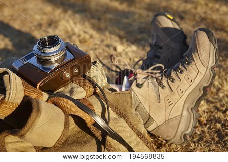 Vintage camera with hiking boots and backpack. Travel background. Horizontal