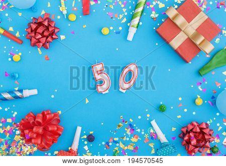 Colorful celebration pattern with various party confetti balloons gift box and number 50 on blue background. Flat lay
