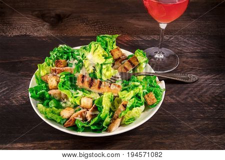 A photo of a plate of chicken Caesar salad with a fork and a glass of rose wine, on a dark rustic background with a place for text