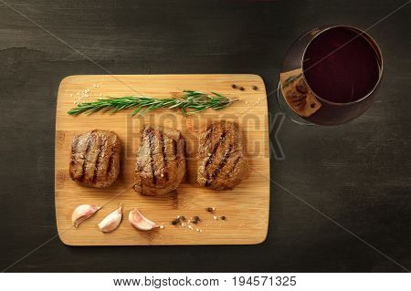 Three slices of cooked meat, beef fillet, shot from above on rustic textures with a sprig of rosemary, garlic cloves, salt, and pepper, with a glass of red wine and a place for text