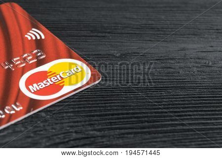 Sankt-Petersburg Russia July 09 2017: MasterCard credit cards logo on office black desk board. close up view of a MasterCard credit card on black wooden table. Photo taken in Sankt-Petersburg Russia July 09 2017